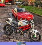 Production (Stock) Ducati Monster Series, a white and red motorcycle parked on the side of the road a red Ducati Monster Series Streetbike parked on the side of the road