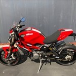 Production (Stock) Ducati Monster Series, a red and black motorcycle parked on the side of a road a red and black Ducati Monster Series Streetbike is parked on the side of a road