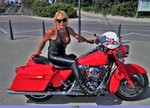 Women Harley-Davidson Road King, Hot babe on a Harley Davidson/Road King motorcycle. a woman wearing a red Harley-Davidson Road King Streetbike parked on the side of a road
