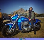 Women Suzuki Marauder Models, Beautiful woman on a Harley Davidson/Unknown (HD) motorcycle. a person standing next to a parked Suzuki Intruder1500 Streetbike posing for the camera