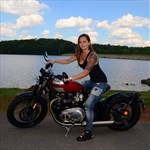 Women Triumph Unknown (Triumph), a person riding a motorcycle next to a body of water a person riding a Triumph  Streetbike next to a body of water