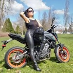 Women Yamaha FZ/MT Models, a woman sitting on a motorcycle in a field posing for the camera